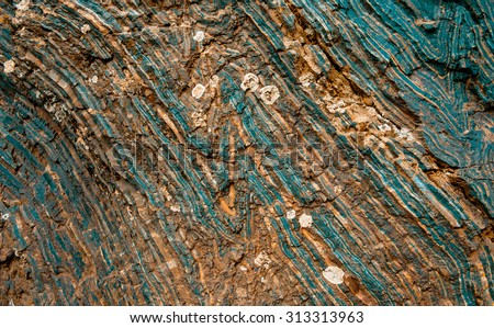 Iron ore texture closeup - natural minerals in the mine. Stone texture of open pit. Extraction of minerals for heavy industry - the texture of the rock containing iron ore and copper. - stock photo