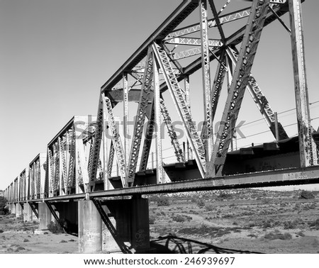 Iron railroad bridge over dry river bed - stock photo
