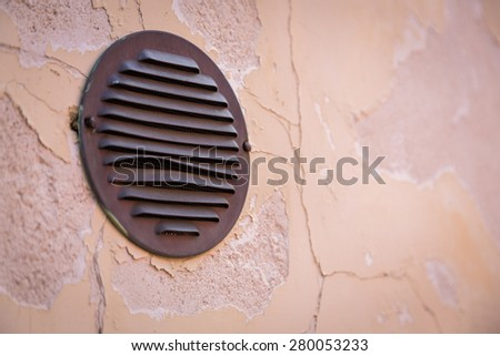 Iron round window in the wall.  - stock photo