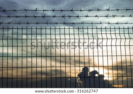 iron wire fence against twilight sky - stock photo