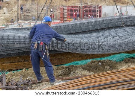 Iron worker unloading reinforcing steel from crane for construction. At construction site. - stock photo
