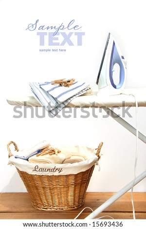 Ironing board with laundry against white background - stock photo
