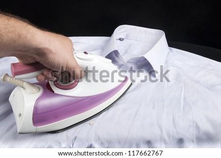 ironing shirt with Hot steam iron on black background - stock photo