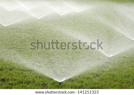 Irrigating grass with water sprinkler - stock photo