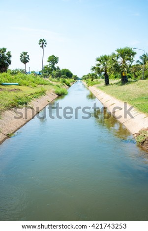 Irrigation canal between agricultural crops. - stock photo