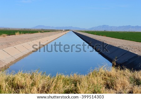 Irrigation canal between agricultural crops in California. - stock photo