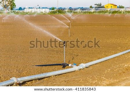 irrigation of cultivated fields with rotating sprayers near photovoltaic panels - stock photo