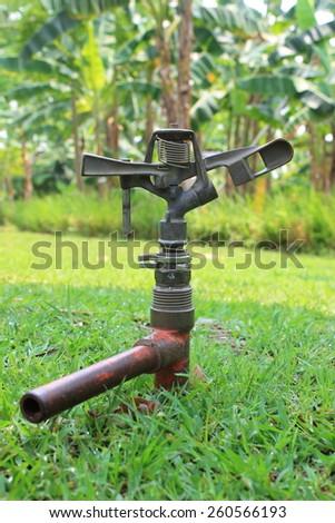 Irrigation sprinkler in the garden - stock photo