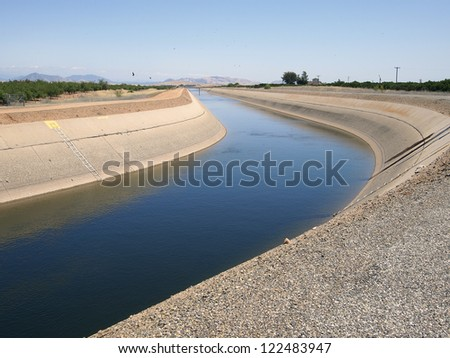 Irrigation water being pumped from reservoirs, through a canal, to agricultural fields. - stock photo