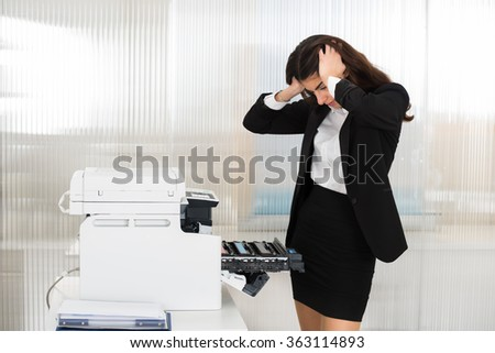 Irritated young businesswoman looking at printer machine at office - stock photo