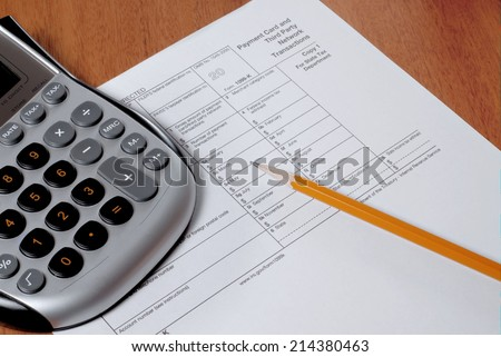 IRS form 1099, a calculator and a sharpened pencil on a wooden desk. The 1009 form is used to record and track the earnings of a freelancer or independent contractor, not a regular employee. - stock photo