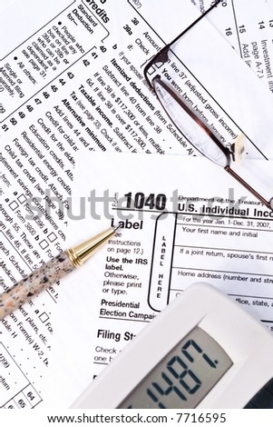 IRS 1040 forms with pen, glasses, and calculator - stock photo