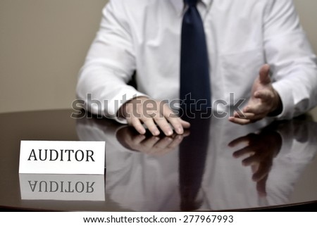 IRS tax auditor business card at desk with hands gesturing - stock photo