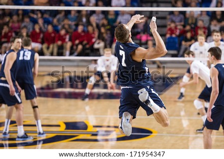 IRVINE, CA - JANUARY 17: Brigham Young University's Phil Fuchs serves in a volleyball match with the University of California - Irvine at the Bren Events Center in Irvine, CA on January 17, 2014 - stock photo