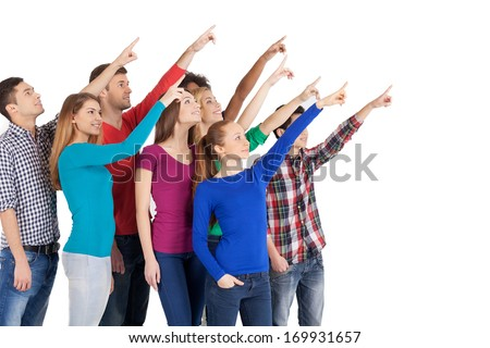 Is it a plane? Group of cheerful young multi-ethnic people standing close to each other and pointing away while standing isolated on white - stock photo