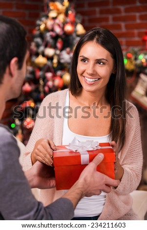 Is it for me? Rear view of young man giving a red gift box to his girlfriend with Christmas Tree in the background  - stock photo