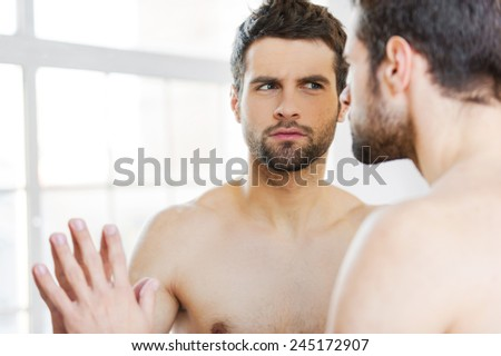 Is that acne? Serious young shirtless man leaning at the mirror and looking at himself attentively  - stock photo