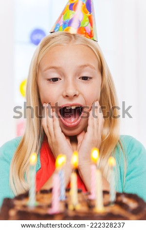Is that all for me? Happy little girl looking at the birthday cake and looking excited - stock photo