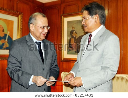 ISLAMABAD, PAKISTAN - SEPT 23: Foreign Affairs Sec, Salman Bashir receives a cheque of thirty thousand dollars to Thailand Ambassador in Islamabad on Friday, September 23, 2011 in Islamabad. - stock photo