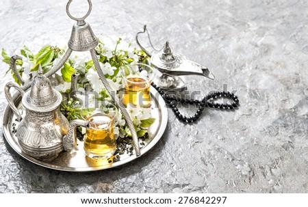 Islamic holidays decoration. Tea glasses and pot, arabian lantern and rosary. - stock photo