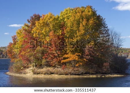 Island of brilliant fall foliage in the lake at Mansfield Hollow reserve in Connecticut on a sunny day with a blue sky. - stock photo