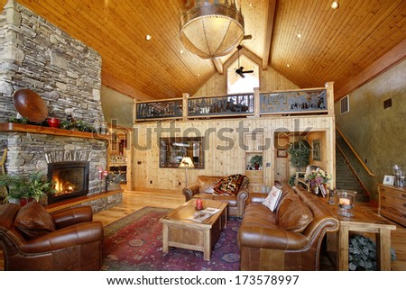 Island Park, Idaho, USA 28 Oct. 2009 The interior of a modern log cabin featuring a stone fireplace, pine paneling, and comfortable furniture. - stock photo