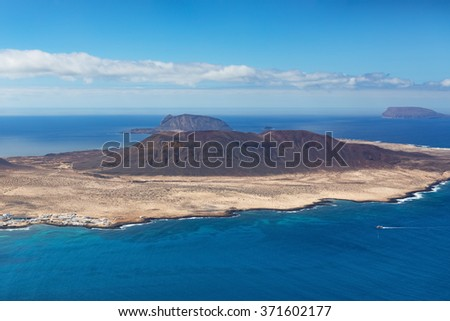 Island. Volcano. Ocean view. Blue sky. La Graciosa - volcanic island in Las Palmas, Canary Islands, Spain. Panoramic view from famous landmark, viewpoint Mirador del Rio on Lanzarote. - stock photo