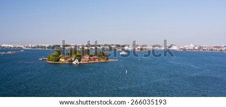 Island with houses and boats docked in Finland on a cloudy day with the capital into the fund - stock photo