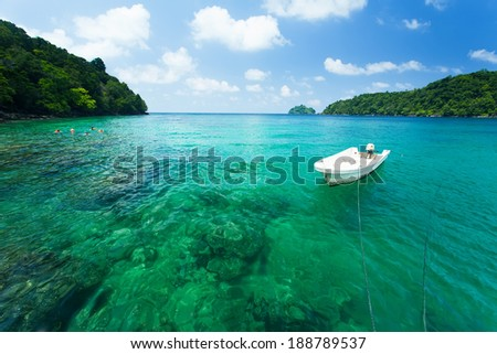 Islands in Indonesia in the turquoise sea with crystal clear water, boat, coral reefs and white sand for diving from a boat. Background blue sky with clouds. - stock photo