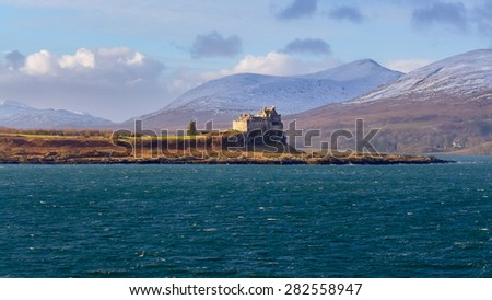 ISLE OF MULL, SCOTLAND JANUARY 24 2015: The sun shines on Duart castle which stands in front of snowy mountains JANUARY 24, 2015 on the Isle of Mull. - stock photo