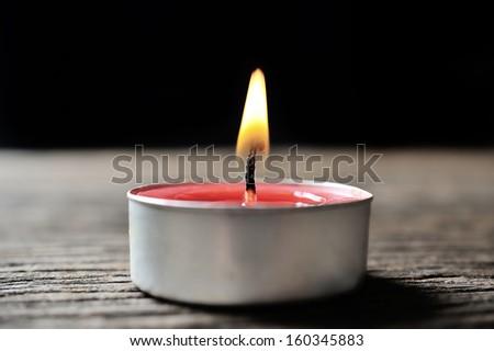 isolate burning candle on dark background - stock photo