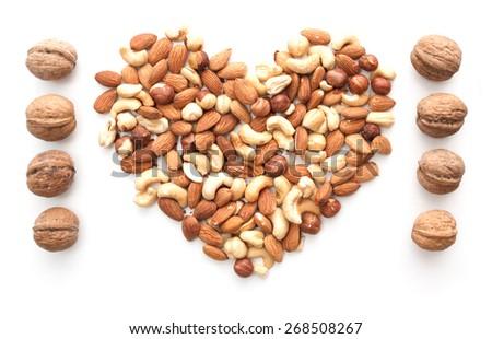 isolated almonds, cashew, hazelnut heart shape and walnut raw - stock photo