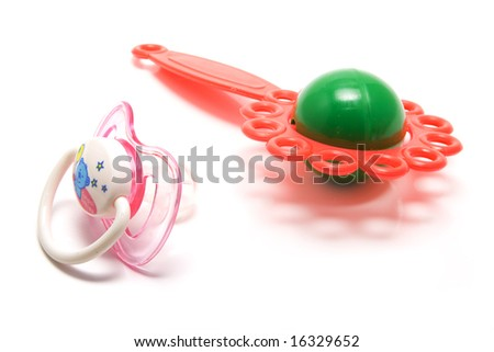 isolated baby's dummy and rattle - stock photo