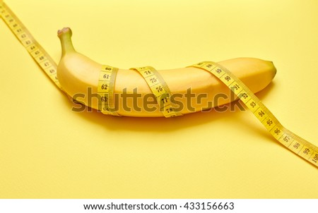 Isolated banana with measuring tape on a yellow background - stock photo