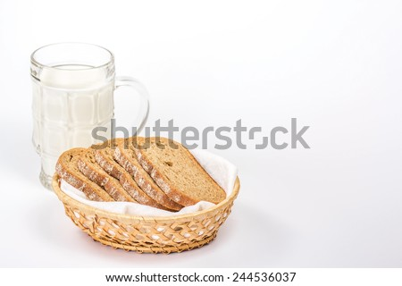 isolated basket of slice bread and glass of milk - stock photo