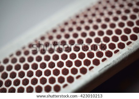 Isolated box of safety matches with its black striking surface with the honeycomb shapes on the narrower side  - stock photo