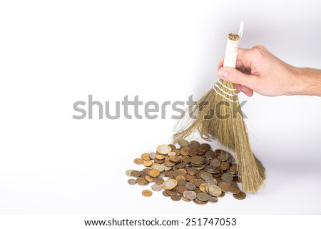 isolated broom in a man's hand and golden coins - stock photo