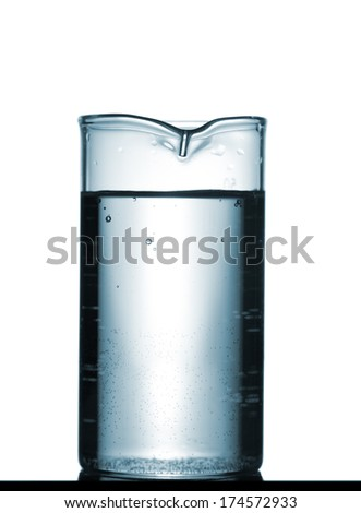 Isolated chemical beaker on table with a small reflection, studio shot - stock photo