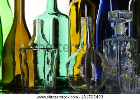 isolated close-up collection of beautiful colored empty bottles on white studio background - stock photo