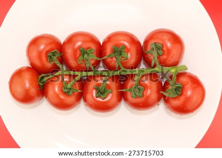 Isolated cluster of fresh ripe red cherry tomatoes close-up on a white plate on red background - stock photo