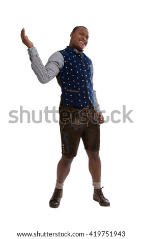 Isolated dark skinned man wearing typical bavarian clothes making promotion for the bavarian beer festival in Munich called Oktoberfest. - stock photo