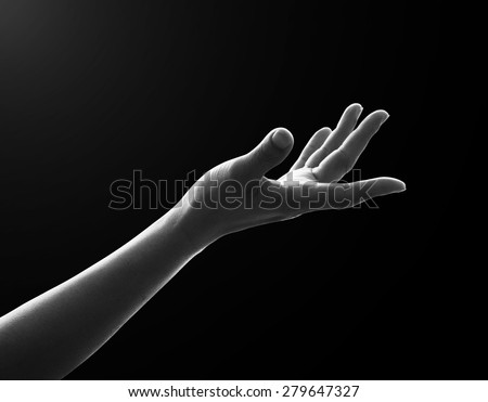Isolated female empty open human hand with palm raised upward in reaching posture in dark black and white color tone: Pray for spiritual support and help concept: Humanitarian aid conceptual idea:  - stock photo