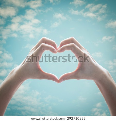 Isolated female human hands in heart shape raising against vintage retro style blue sky background: Universal hand sign language expression meaning love, caring, friendship, peace - stock photo