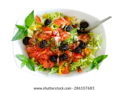 Isolated fresh plain salad garnished with sprigs of mint containing lettuce, tomato, sweet peppers and black olives served in a bowl with a fork - stock photo