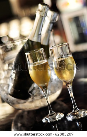 Isolated glasses of champagne with bottle background - stock photo
