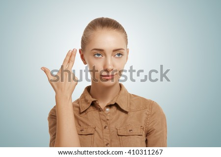 Isolated headshot of young woman committing suicide with finger gun gesture. Portrait of bored girl shooting herself making finger pistol sign against blue wall background. Human face expressions  - stock photo