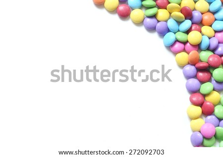 Isolated heap of colored smarties on white background shape like right frame - stock photo