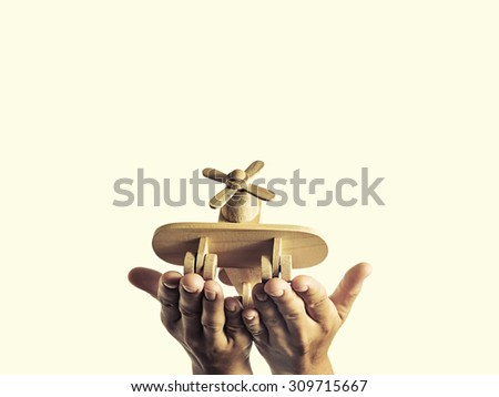 Isolated image of an open palms with a wooden hand-made aircraft - stock photo