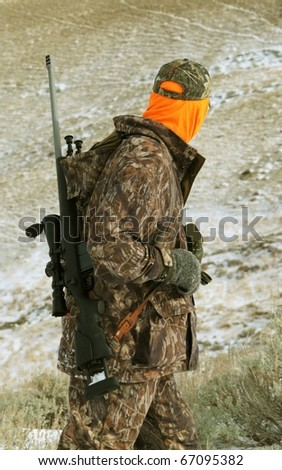 Isolated image of hunter with rifle.  Image taken while hunting big-game in Wyoming. - stock photo