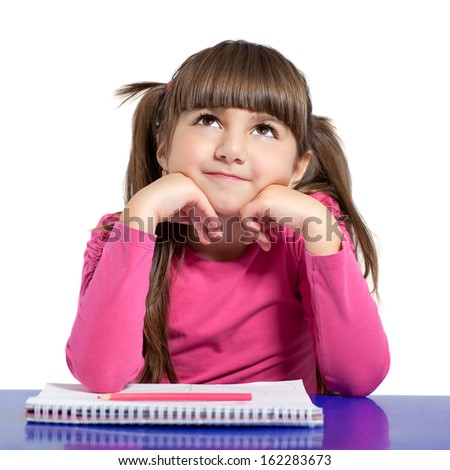 isolated little girl in a pink shirt is sitting at the table and draws - stock photo